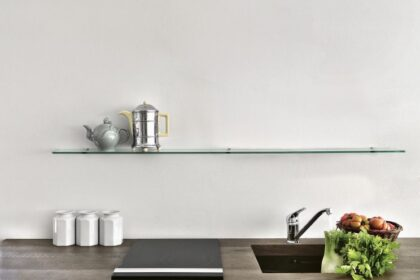 close-up of a wooden worktop of the kitchen with ceramic hob and integrated sink in which there are some vedetables, above them there is a glass shelf with a silver teapot and a coffee pot
