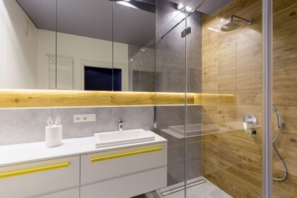Mirrors above white cabinets with yellow handles in modern bathroom interior with glass shower door